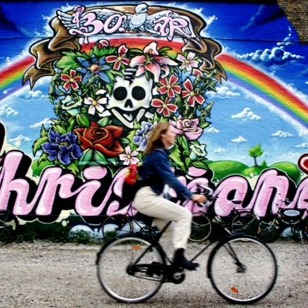 Visit Freetown Christiania and meet the real Hippies  Freetown Christiania is a green and car-free neighborhood in Copenhagen, best known for its autonomous inhabitants' different way of life. It was established in 1971 by a group of hippies who occupied some abandoned military barracks on the site and developed their own set of society rules, completely independent of the Danish government.