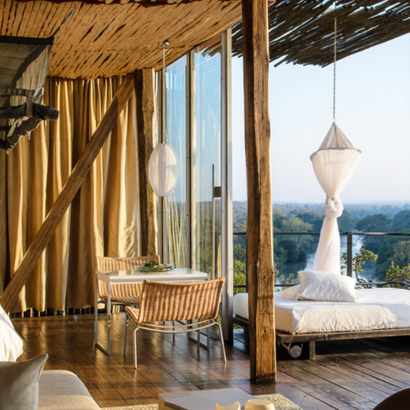 Stay at a beautiful safari lodge overlooking a bustling watering hole