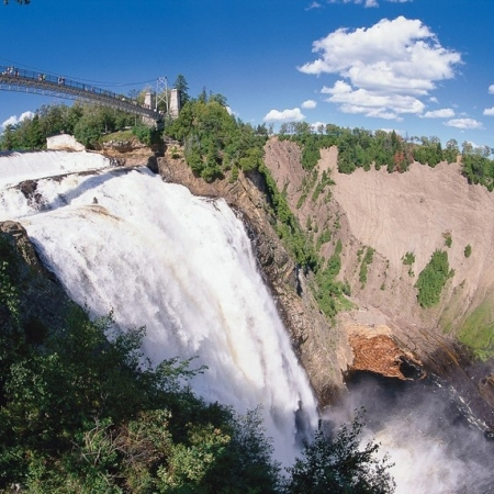 "This natural phenomenon is definitely not to be missed! At 83 m high (30 m higher than Niagara Falls) Montmorency Falls can be seen from all the way across the St. Lawrence River in Lévis! But the best views are from Parc de la Chute-Montmorency, where you can feel the full force—and spray—of the falls for yourself. In winter the spray freezes at the foot of the falls to form a huge ""sugar loaf,"" another intriguing Québec City attraction."